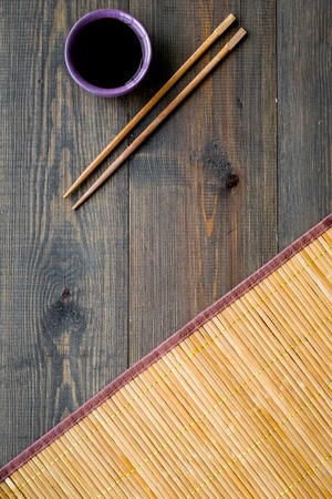 Chinese meal concept. soy sauce in bowl near chopsticks and bamboo table mat on dark wooden background.