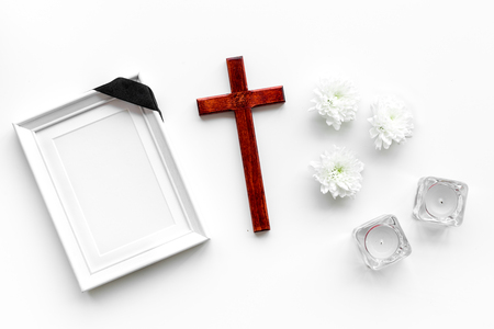 Funeral. Mockup of portrait of the deceased, of dead person. Frame with black ribbon near flowers, candles and cross on white background top view Zdjęcie Seryjne - 112254670