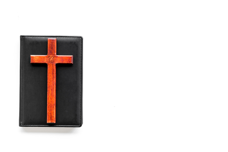 Farewell ceremony, funeral concept. Wooden cross on Bible on white background top view space for text Zdjęcie Seryjne