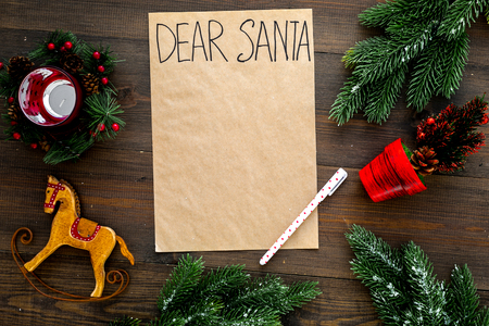 Letter to Santa Claus template. Mockup on craft paper with text Dear Santa near New Year decoration like fir branches, candle, toy horse on dark wooden background top view 版權商用圖片