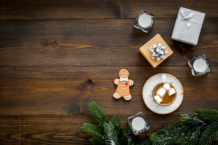 New Year or Christmas concept with hot drink. Cocoa with marshmallow, gift box, gingerbread man, candles, fir branches on dark wooden background top view copy space