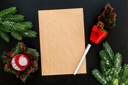 New Year or Christmas mockup. Template for letter to Santa, list of plans and goals for New Year, wishlist near fir branches, candle, festive tree on black background top view