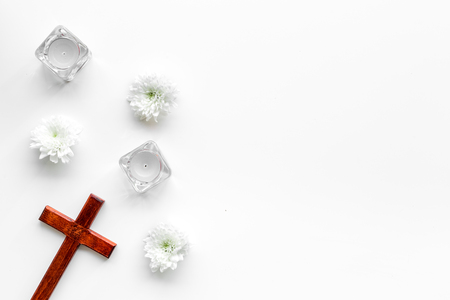 Funeral concept. Wooden cross near candles and flowers on white background top view copy space