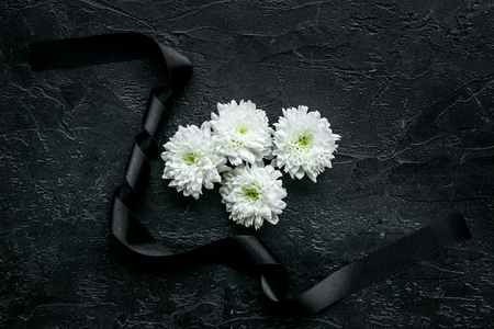 Funeral symbols. White flower near black ribbon on black background top view space for text Zdjęcie Seryjne - 112254817