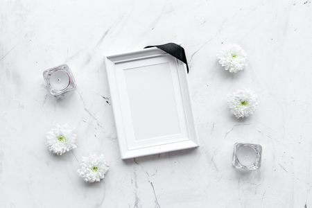 Death concept. Photo frame, mockup with black ribbon near flowers, candles on white stone background top view Banque d'images