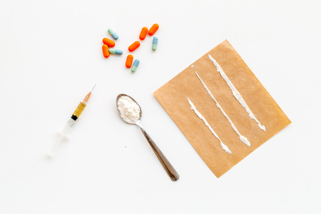 Take drugs, drugs addiction concept. White powder like heroine or cocaine, drug tracks pills, spoon, syringe on white background top view. Reklamní fotografie