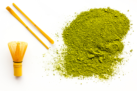 Matcha powder near specail stick and whisk on white background top view. Reklamní fotografie