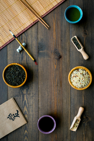 Chinese traditional symbols concept. Tea, rice, hieroglyph love, bamboo table mat, chopsticks, soy sauce on dark wooden background top view frame space for text