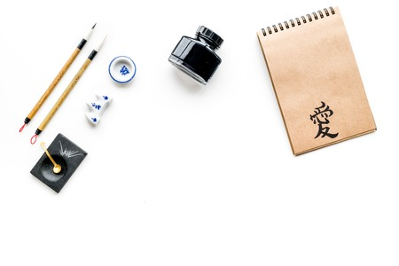 Chinese or Japanese calligraphy pattern. Hieroglyph love in craft paper notebook and writing accessories on white background top view space for text 스톡 콘텐츠