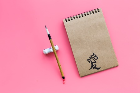 Chinese traditional calligraphy concept. Asian hieroglyph love in craft paper notebook near special writing pen on pink background top view copy space