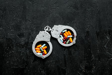 Arrest for illegal purchase, possession and sale drugs concept. Drugs as pills near handcuff on black background top view copy space