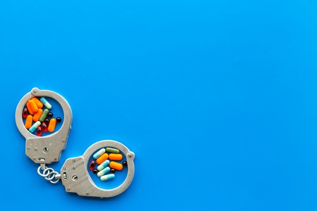 Arrest for illegal purchase, possession and sale drugs concept. Drugs as pills near handcuff on blue background top view space for text