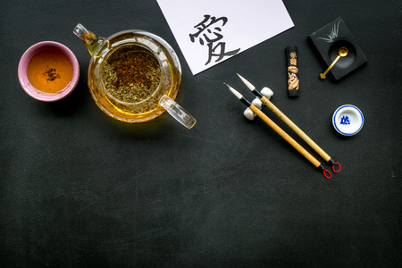 Chinese or Japanese traditions. Calligraphy and tea ceremony concept. Special writing pen, ink near teapot and cup of tea, hieroglyph love on black background top view copy space