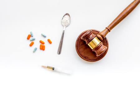 Drugs addiction, arrest for drugs. Pills, spoon with powder, syringe on white background top view
