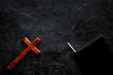Farewell ceremony, funeral concept. Wooden cross on Bible on black background top view space for text Zdjęcie Seryjne