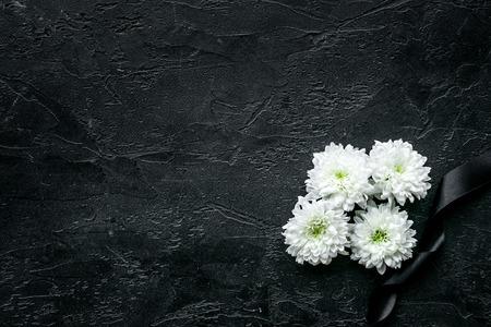 Begräbnissymbole. Weiße Blume in der Nähe von schwarzem Band auf schwarzem Hintergrund Draufsichtraum für Text