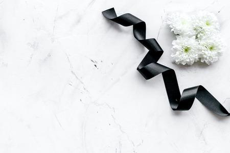 Funeral symbols. White flower near black ribbon on white stone background top view copy space Stockfoto - 112334085