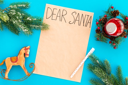 Letter to Santa Claus template. Mockup on craft paper with text Dear Santa near New Year decoration like fir branches, candle, toy horse on blue background top view