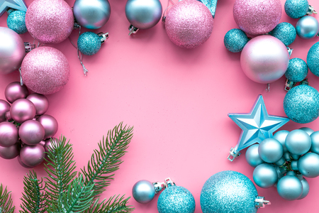 New Year and Christmas atmosphere. Decorate festive Christmas tree. Christmas tree decoration. Colorful balls and stars near spruce branch, pine fir on pink background top view space for text