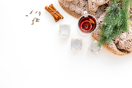 Hot beverage for warm winter evening. Mulled wine near fir branches, wool blanket, candles on white background top view space for text Stock Photo