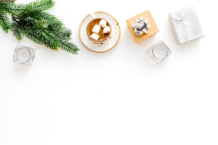 New Year or Christmas concept with hot drink. Cocoa with marshmallow, gift box fir branches on white background top view copy space