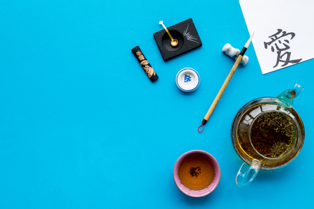 Lesson of calligraphy concept. Paper with hieroglyph love near writing accessories, teapot and cup of tea on blue background top view copy space Imagens