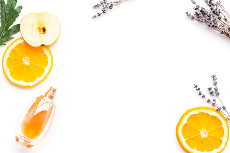 Sweet perfume with fruit fragrance. Bottle  of perfume near apple, orange, lavender on white background top view copy space border Stock Photo