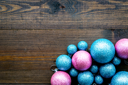 Toys for New Year tree 2019 background. Blue and pink balls on dark wooden background top view copy space border
