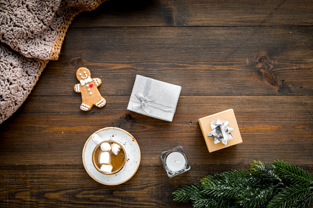Romantic winter composition with hot drink. New Year or Christmas Eve. Cocoa with marshmallow, gift box, gingerbread man, wool blanket, fir branches on dark wooden background top view copy space