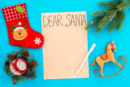 Letter to Santa Claus template. Mockup on craft paper with text Dear Santa near Christmas decoration like fir branches, candle, socks on blue background top view