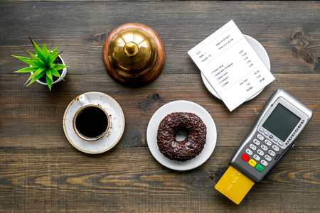 Electronic payments. Pay the bill by card concept. Bank card inserted in payment terminal near bill, service bell, coffee and donut on dark wooden background top view copy space 写真素材