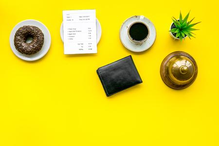 Paga la cuenta, paga en el restaurante. Verifique cerca de la billetera, la campana de servicio, el café en el espacio de vista superior de fondo amarillo para el texto