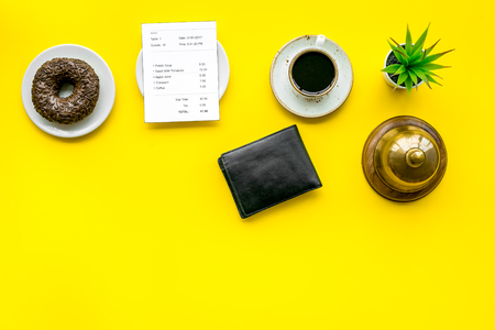 Pay the bill, pay at restaurant. Check near wallet, service bell, coffee on yellow background top view space for text Archivio Fotografico