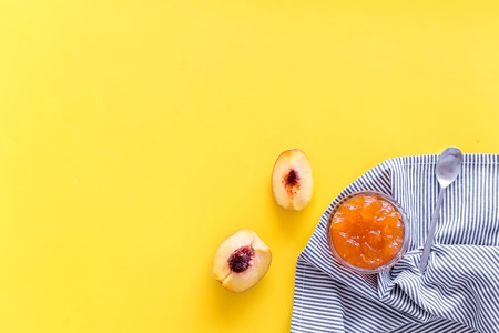 Fruit dessert. Peach jam in jar near slices of fresh peaches and spoon on yellow background top view copy space