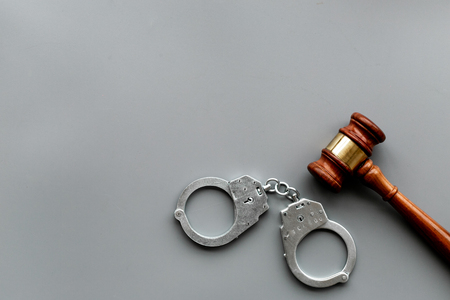 Crime concept. Metal handcuffs near judge gavel on grey background top view space for text