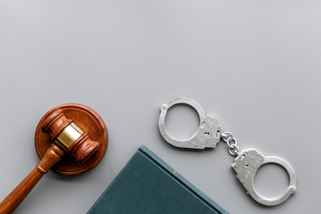 Arrest concept. Metal handcuffs near judge gavel and law book on grey background top view space for text Stock Photo