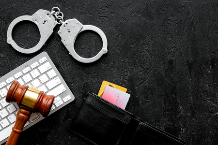 Arrest for stealing money online concept. Handcuff near keyboard, judge gavel and bank card on black background top view copy space