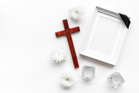 Funeral. Mockup of portrait of the deceased, of dead person. Frame with black ribbon near flowers, candles and cross on white background top view copy space Zdjęcie Seryjne