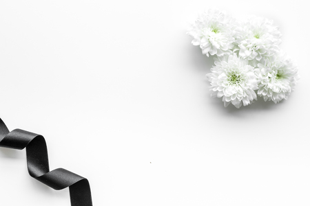 Funeral symbols. White flower near black ribbon on white background top view copy space Stock Photo