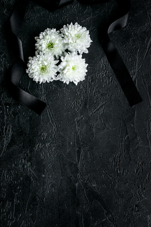 Funeral symbols. White flower near black ribbon on black background top view copy space