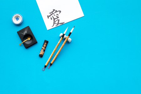 Chinese or Japanese calligraphy concept. Hieroglyph love near traditional written accessories on blue background top view copy space Reklamní fotografie