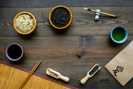Chinese traditional symbols concept. Tea, rice, hieroglyph love, bamboo table mat, chopsticks, soy sauce on dark wooden background top view frame copy space