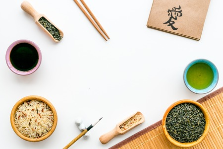 Chinese traditional symbols concept. Tea, rice, hieroglyph love, bamboo table mat, chopsticks, soy sauce on white background top view frame copy space