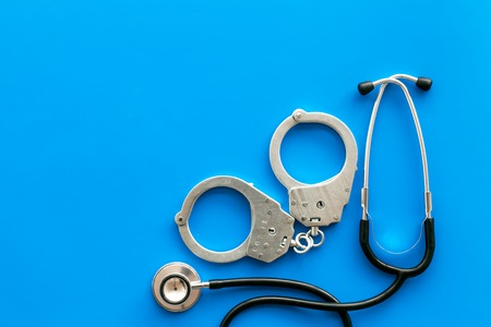 Medical lawsuit. Arrest for medical crime concept. Handcuff near stethoscope on blue background top view copy space