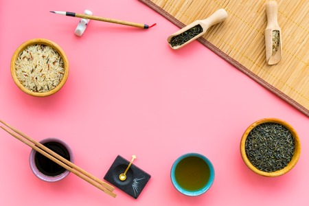 Chinese traditional symbols concept. Tea, rice, hieroglyph love, bamboo table mat, chopsticks, soy sauce on pink background top view frame copy space Stock Photo
