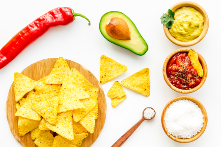 Popular Mexican snack nachos. Triangle nacho tortilla near salsa and guacamole sauce, chili pepper, salt on white background top view Stock Photo