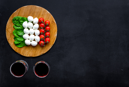Italian cuisine, food concept. Italian flag made of mozzarella, tomatoes, basil on wooden cutting board near glass of red wine on black background top view space for text Reklamní fotografie - 112469983