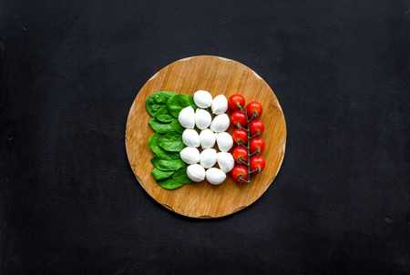 Italian flag made of mozzarella cheese, cherry tomatoes, green basil on wooden cutting board on black background top view space for text