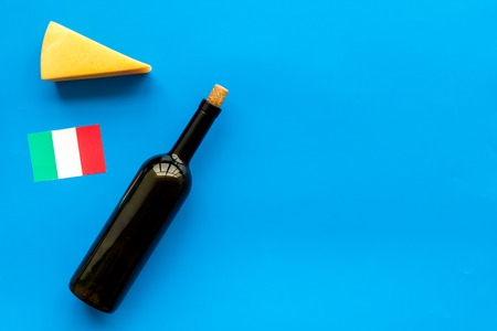 Gastronomical tourism. Italian food symbols. Italian flag, cheese parmesan and bottle of red wine on blue background top view copy space Reklamní fotografie - 112469991
