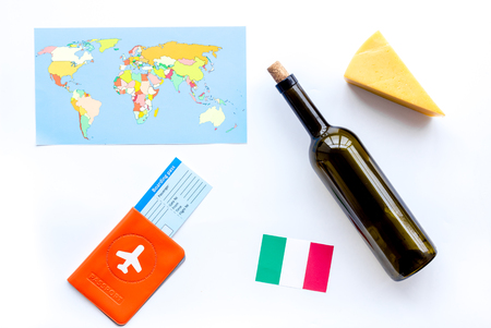 Gastronomical tourism. Italian food symbols. Passport and tickets near italian flag, bottle of red wine, map of the world, cheese parmesan on white background top view